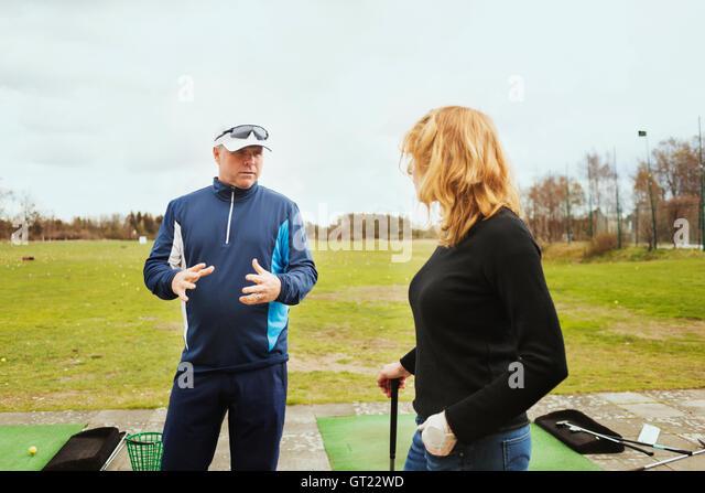 Man talking with woman while standing at driving range - Stock-Bilder