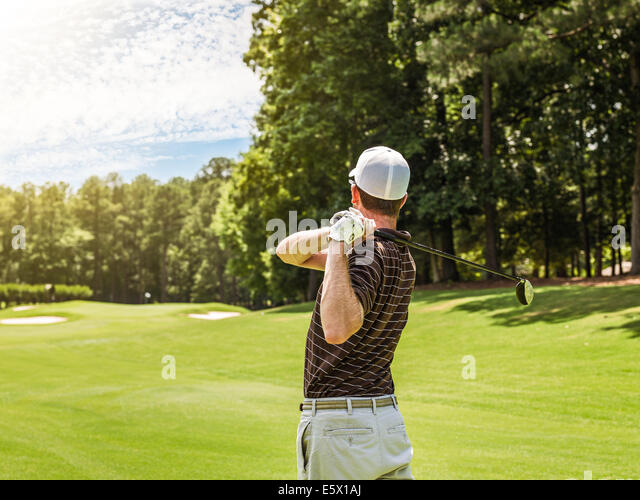 Rear waist up view of young male golfer teeing off on golf course, Apex, North Carolina, USA - Stock Image