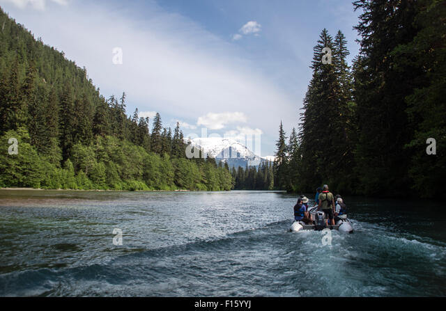 A wilderness guide and tourists travel up a remote river by zodiac in the Great Bear Rainforest of British Columbia, - Stock-Bilder