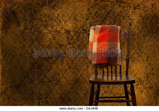 Old blanket on back of antique chair in room with vintage wallpaper - Stock Image