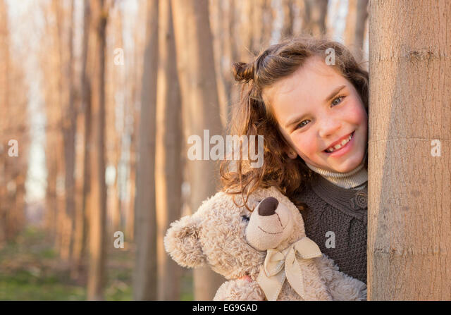 Girl hiding behind tree trunk with her teddy bear - Stock Image