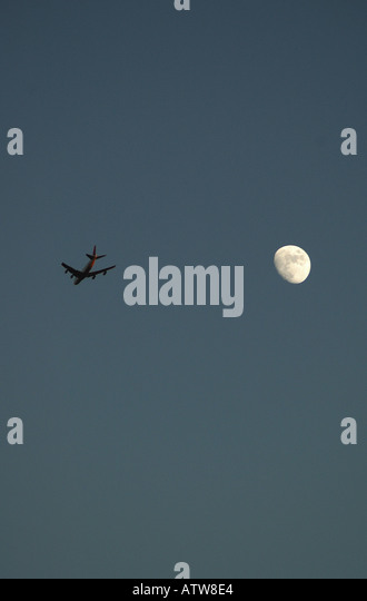 Red Eye Flight Passing The Moon - Stock Image