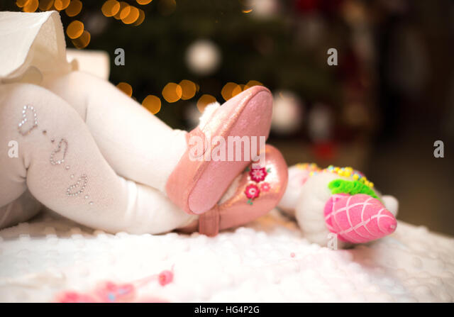 baby girl legs wearing shoes with bokeh - Stock Image