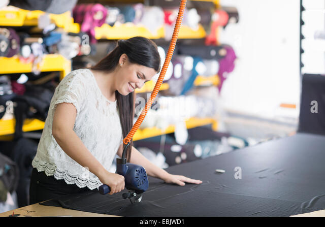 Young seamstress using cutting machine on textile at work table - Stock Image