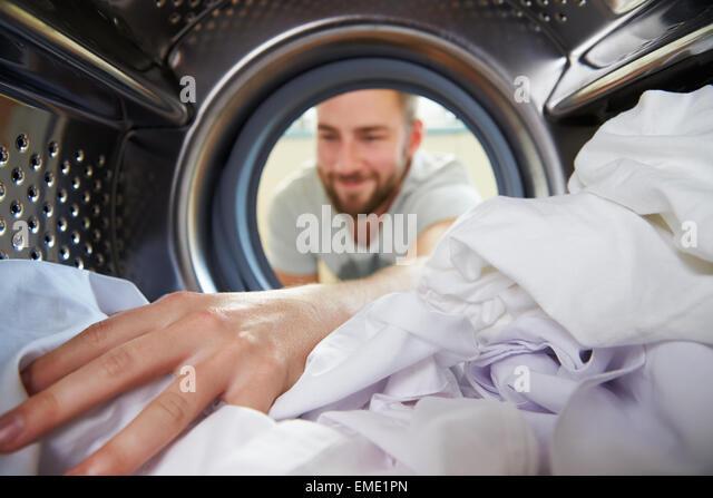 Man Doing Laundry Reaching Inside Washing Machine - Stock Image