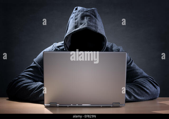 Computer hacker stealing data from a laptop - Stock-Bilder