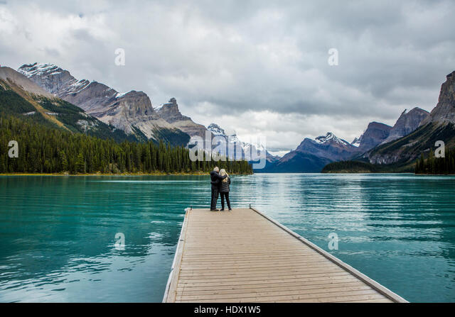 Caucasian couple standing at the end of dock on mountain lake - Stock Image