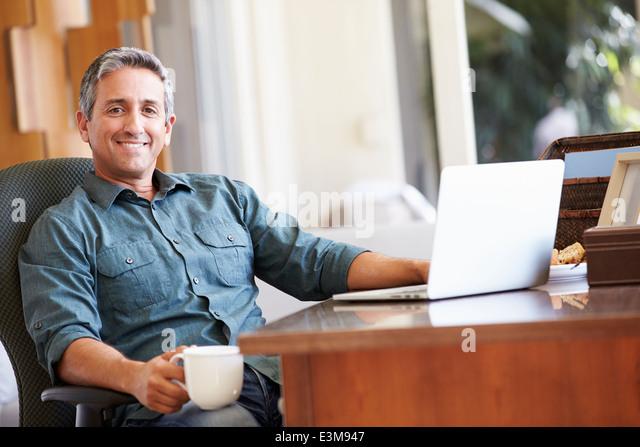 Mature Hispanic Man Using Laptop On Desk At Home - Stock Image