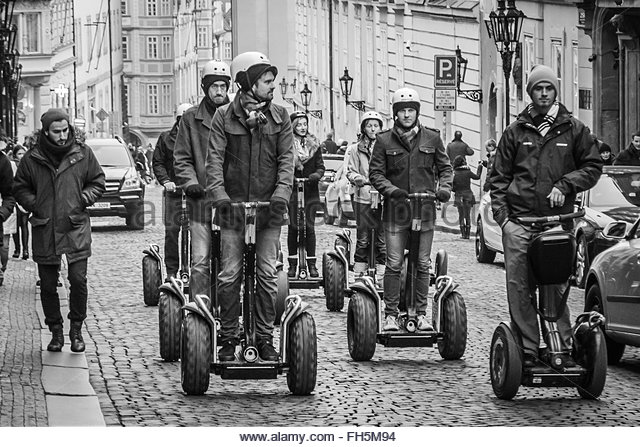 Prague, Czech Republic - 2 January 2014:  Monochrome image showing group of tourists riding segways along steep - Stock Image