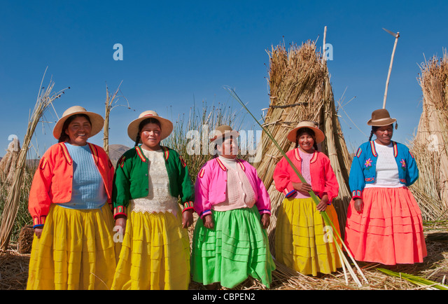 Lake Titicaca Peru with local traditional women of Uros Tribe history in colorful clothes near Puno - Stock-Bilder