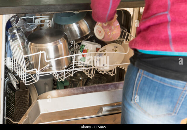 Mid section view of woman taking tea cup from dishwasher, Bavaria, Germany - Stock-Bilder