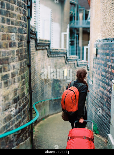 A woman walling down a narrow street, pulling a suitcase and holdin an orange backpack. - Stock Image