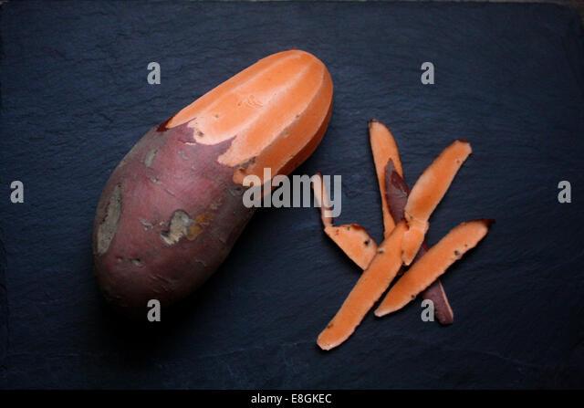 Half peeled Sweet Potato - Stock Image