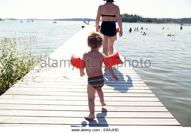 Rear view of male toddler following mother along lake pier - Stock Image