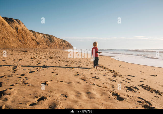 Young boy standing on beach, looking at sea, rear view, Buellton, California, USA - Stock-Bilder