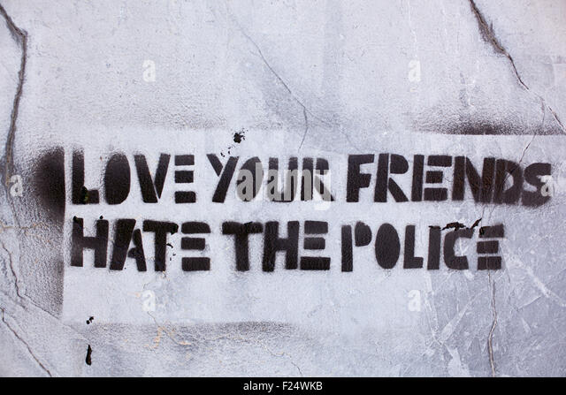Write in the wall: love your friends hate the police - Stock Image