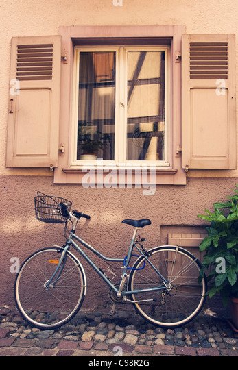 Bike parked under a window, cross process - Stock Image