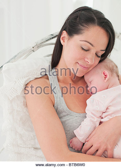 Smiling mother holding sleeping baby - Stock Image