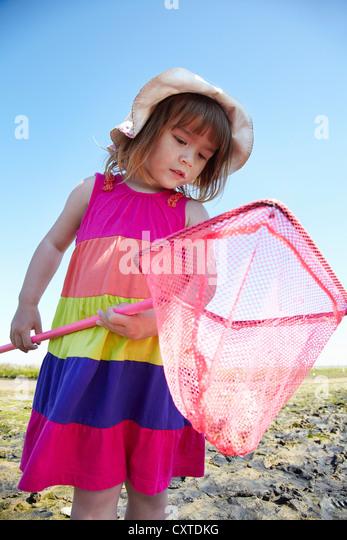 Girl examining fishing net outdoors - Stock Image