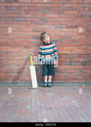 Boy with cricket bat against brick wall - Stock Image