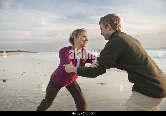 Young man and woman wrestling at beach - Stock Image
