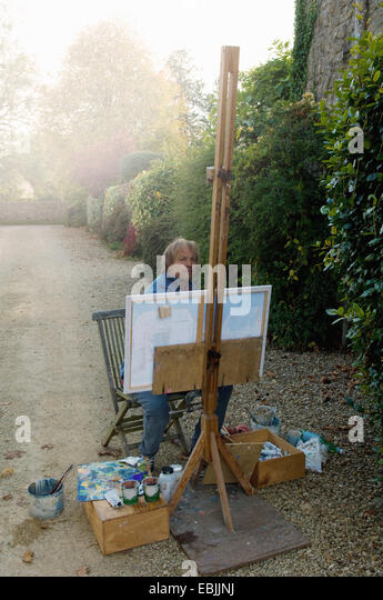 Mature male artist painting canvas on house driveway - Stock-Bilder