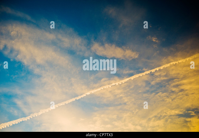 Commercial airline jet contrails across a clear dusk sunset blue sky - Stock Image