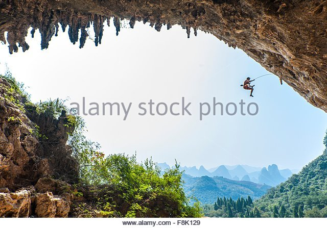 Male climber taking a fall at Odin's Den next to Moon Hill in Yangshuo, Guangxi Zhuang, China - Stock Image