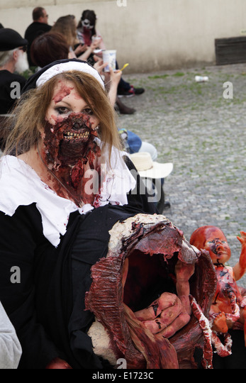 Woman at the yearly zombie walk in Prague, dressed up as a nurse, pretening to have an open womb with a baby - Stock Image