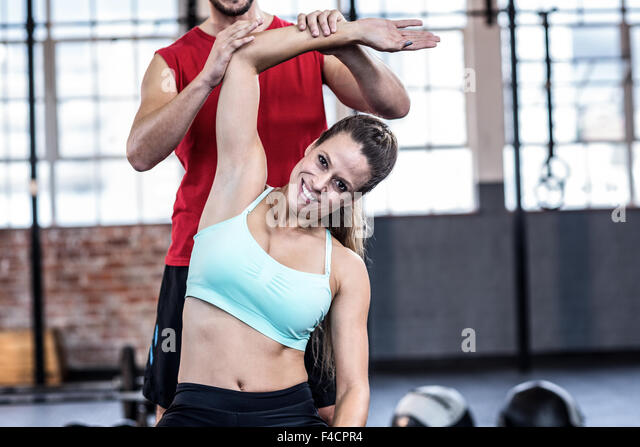 Coach assisting woman stretching - Stock Image