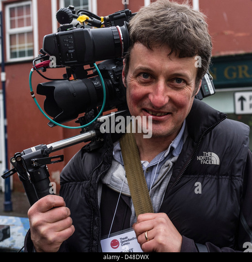 A professional videographer using a Nikon D800 dslr video camera in a shoulder rig, UK - Stock Image