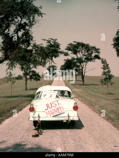 1950s COUPLE BRIDE AND GROOM RIDING IN FORD SEDAN ON BEGINNING OF LONG ROAD JUST MARRIED SIGN AMERICANA NOSTALGIA - Stock Image