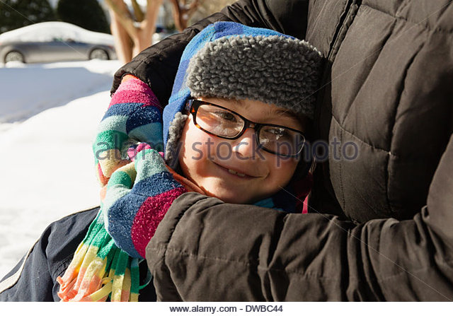 Mother hugging son wearing winter hat and glasses - Stock Image