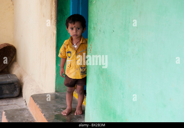 Indian village boy standing in the doorway of his home in Bukkapatnam, Andhra Pradesh, India - Stock Image