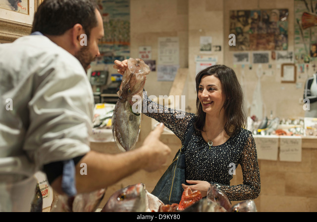 Woman buying fresh fish fishmonger - Stock Image