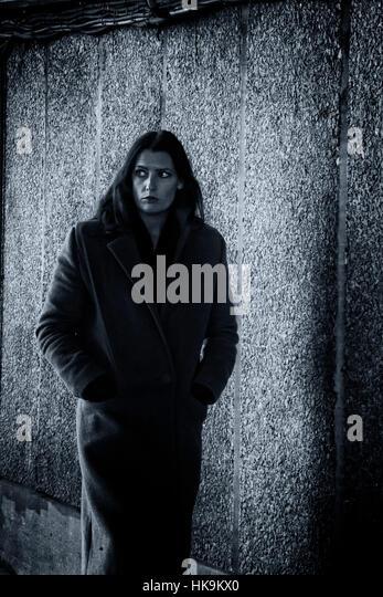 A nervous woman walks through an underpass in a Film Noir style - Stock Image