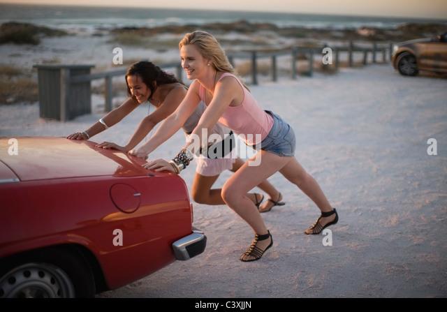Girls pushing their broken car - Stock Image
