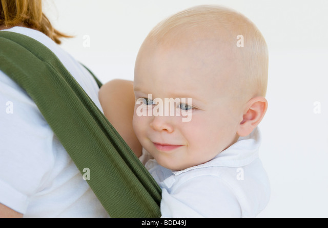 Woman carrying her son in a baby carrier - Stock Image
