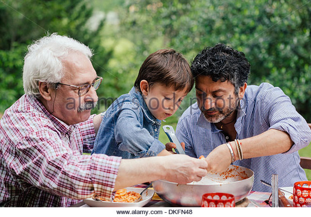 Three generations of male family enjoying a meal together - Stock Image