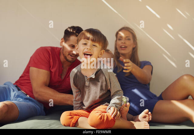 Happy little boy sitting on patio with his family at the back. Focus on little boy sitting in front with his parents - Stock Image