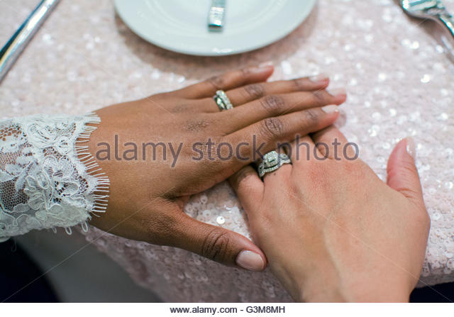 Bride couple's hands wearing wedding bands and engagement rings at wedding reception - Stock Image