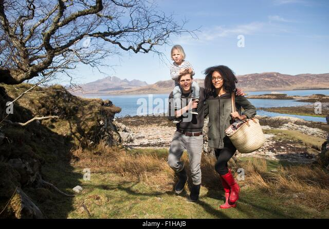 Family on walk, father carrying son on shoulders, Loch Eishort, Isle of Skye, Scotland - Stock Image