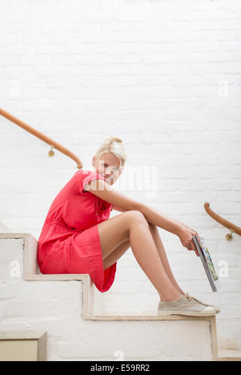 Woman sitting on steps of modern house - Stock Image