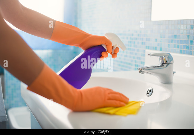 woman doing chores in bathroom at home, cleaning sink and faucet with spray detergent. Cropped view - Stock Image