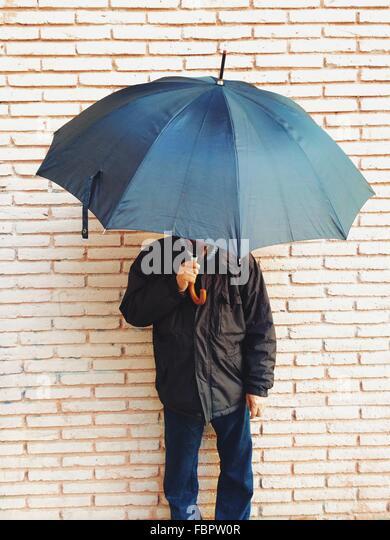 Mature Man Holding Umbrella Against Brick Wall - Stock Image