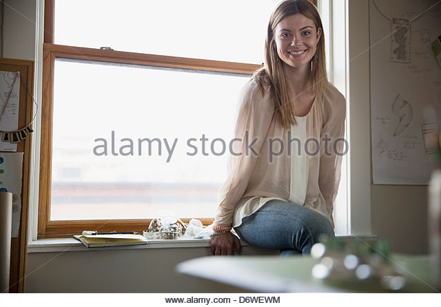 Portrait of beautiful woman smiling by window - Stock Image
