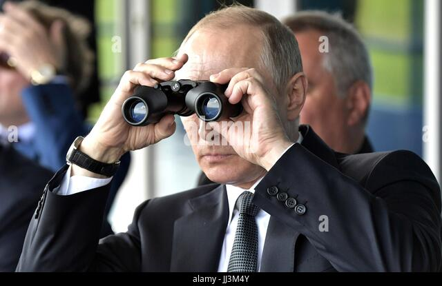 Zhukovsky, Russia. 18th July, 2017. Russian President Vladimir Putin uses binoculars to watch an aircraft aerobatic - Stock Image