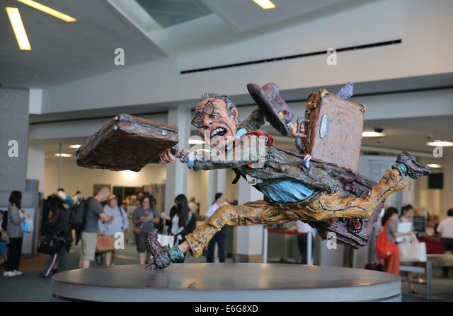man traveling sculpture inside Vancouver airport 'The Flying Traveler' - Stock Image