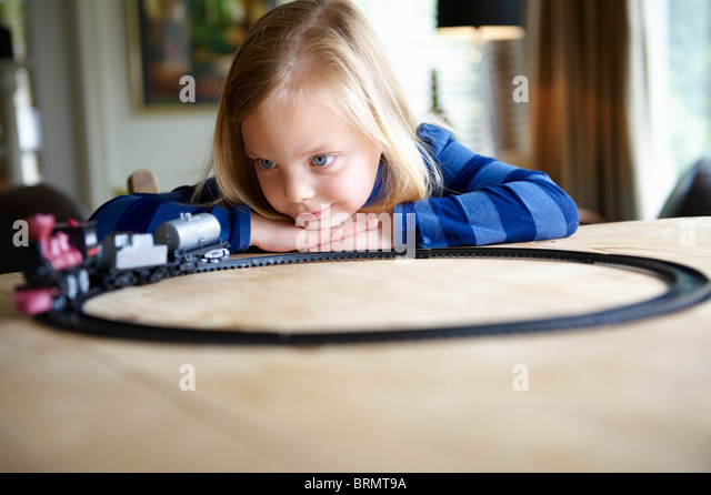 Girl playing with a toy train - Stock Image