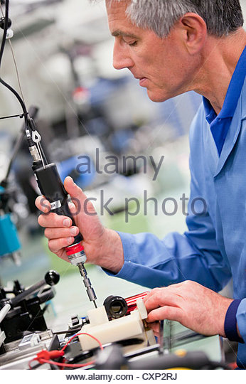Technician working in hi-tech electronics manufacturing plant - Stock Image